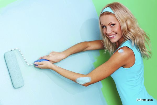woman paints the wall roller