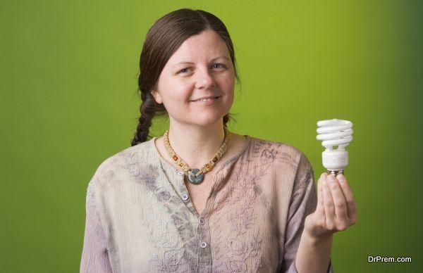 an environmentalist holds a compact fluorescent light bulb