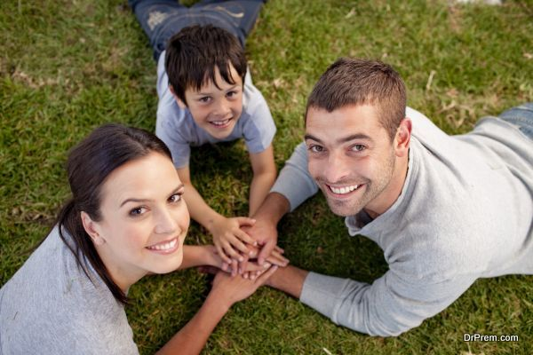 Happy parents and kid lying on garden with hands together