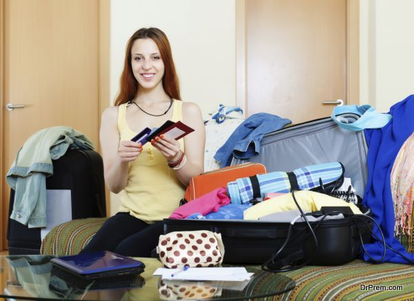 Young woman packing documents into suitcases